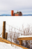 Red Barn in the snow with a rustic fence. A red barn in the snow with an old rustic fence in the foreground stock photography