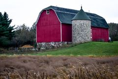 Red Barn with Stone Silo and Cone Top. A red barn with a stone silo with a cone top in the Wisconsin countryside stock photos