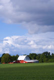 Red barn with storm clouds. A dramatic view of a classic red barn in Oregon's Willamette Valley is nestled between a green field in the foreground and puffy Royalty Free Stock Images
