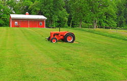 Red Barn Tractor Green Lawn. Red farm barn with old tractor and green lawn in Summer Stock Photo