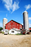 Red barn and two silos. Family farm, with red barn, two silos, and assorted farm equipment, all under a bright blue sky. Barn built in 1872. Located in rural royalty free stock images