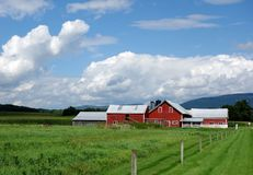 Red Barn on Vermont Landscape. An old red barn of a dairy farm in Vermont in the setting of the green mountains in the Champlain Valley Stock Photos
