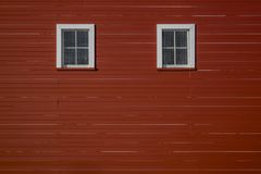 Red barn wall with windows. Two windows that look like eyes on the side of a red barn in rural Iowa Midwest, USA Stock Photography