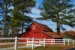 Red barn and white fence. Red barn behind a white fence Royalty Free Stock Photography