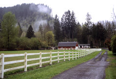 Red barn with white fence on misty day Royalty Free Stock Image