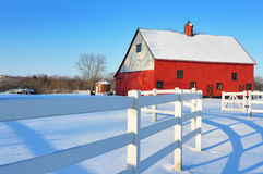Red barn with a white fence with a snow landscape Stock Image