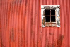 Red barn and window. Dirty, corrugated side of a red barn and dilapidated window Royalty Free Stock Image