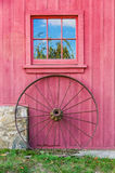 Red Barn, Window and Wagon Wheel. Window in red barn wall, below which rests a large rusted iron wagon wheel against wall and stone foundation Stock Photo