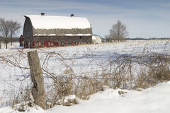 Red barn in winter. With snow in field and old fence in foreground Royalty Free Stock Photo