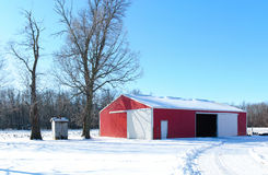 Red barn in winter. Red barn building covered by snow Royalty Free Stock Photography