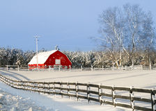 Red Barn in Winter. A Red barn in wintertime with fence in foreground and snow Royalty Free Stock Images