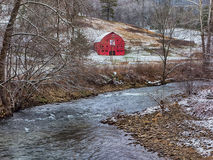 Red barn in winter near a mountain river Stock Photography