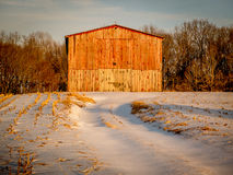 Red Barn in the Winter. An old wooden red barn surrounded by snow glows from a sunset in the winter Royalty Free Stock Image