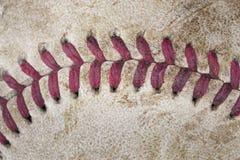 A red baseball seam. A closeup of a dirty baseball seam stock photo