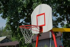 Red basketball hoop on a white backboard on the street. On the sports field stock photo
