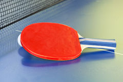 Red bat, tennis ball on blue ping pong table Stock Photos