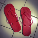 Red bath flip flops on white tiles Royalty Free Stock Images