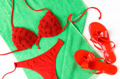 Red bathing suit and red flip-flops on green towel. Summer cloth Stock Images