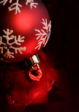 Red Bauble. A single red christmas ornament illuminated on glossy red paper Royalty Free Stock Images