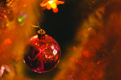 Red bauble in Christmas tree surrounded by colourful lights Royalty Free Stock Image