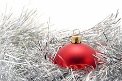 Red Bauble in garland. Red christmas bauble in silver garland isolated on white with copyspace royalty free stock photos