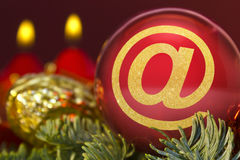 Red bauble with the golden shape of an at symbol. series. A glossy red bauble with the golden shape of an at symbol.series stock images