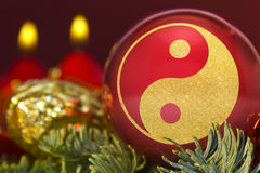 Red bauble with the golden shape of a YingYang symbol. series. A glossy red bauble with the golden shape of a YingYang symbol.series royalty free stock photo