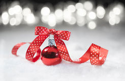Red bauble with matching ribbon on snow Royalty Free Stock Photos
