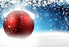 Red bauble over winter background. Stock Photo