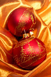 Red baubles on golden cloth Royalty Free Stock Images