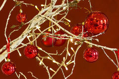 Red baubles hanging from a decorated Christmas Tree Royalty Free Stock Images