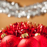 Red baubles with shiny tape in background Stock Images