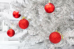 Red baubles on silver artificial christmas tree Stock Images