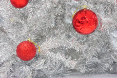 Red baubles on silver artificial christmas tree Royalty Free Stock Photography