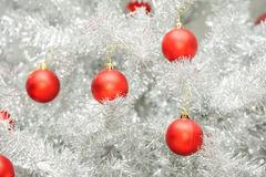 Red baubles on silver artificial christmas tree Royalty Free Stock Images