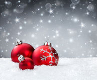 Red baubles on snow. With silver sparkle background stock photography