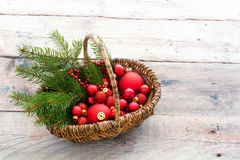 Red baubles to decorate the Christmas tree in a basket on rustic Royalty Free Stock Image