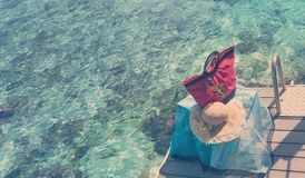 Red beach bag and straw hat on sea  background, retro effect.  Royalty Free Stock Photos