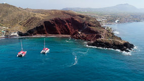 Red beach with catamarans in Santorini, Greece Stock Photos