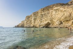 Matala , Red beach. Red Beach, near Matala, Crete, Greece , Europe . Nudist and hippie beach. People swimming in the sea water Stock Images