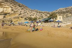 Matala , Red beach. Red Beach,  near Matala, Crete, Greece , Europe . Nudist and hippie beach. The young boy and mum  is playing with sand on the beach Stock Photography