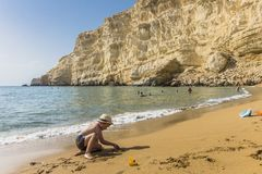 Matala , Red beach. Red Beach,  near Matala, Crete, Greece , Europe . Nudist and hippie beach. The young boy is playing with sand on the beach Royalty Free Stock Photos