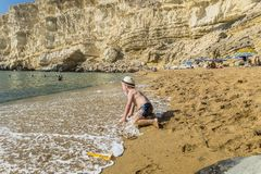 Matala , Red beach. Red Beach,  near Matala, Crete, Greece , Europe . Nudist and hippie beach. The young boy is playing with sand on the beach Royalty Free Stock Image