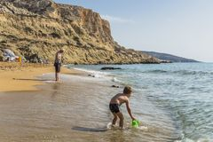Matala , Red beach. Red Beach,  near Matala, Crete, Greece , Europe . Nudist and hippie beach. The young boy is playing with sand on the beach Stock Image