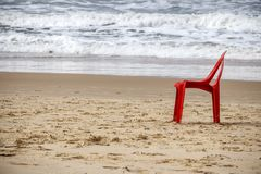 Red beach plastic chair on the sand close to the water Stock Images