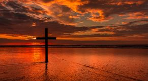 Red Beach Salvation. Dark cross on a beach with a red sunset sky Stock Images