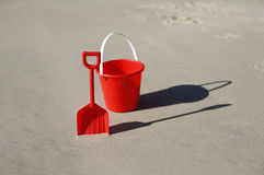 Red beach toys. A red plastic bucket and spade on the beach stock photo