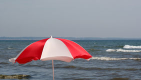 Red Beach Umbrella. A beach umbrella set against the sea Royalty Free Stock Photography