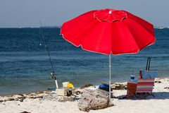 Red Beach Umbrella. Shades a spot in the sand with a beach chair, cooler and fishing tackle stock photo