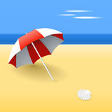 Red beach umbrella. Beach umbrella on a beach, with a scallop shell Royalty Free Stock Image
